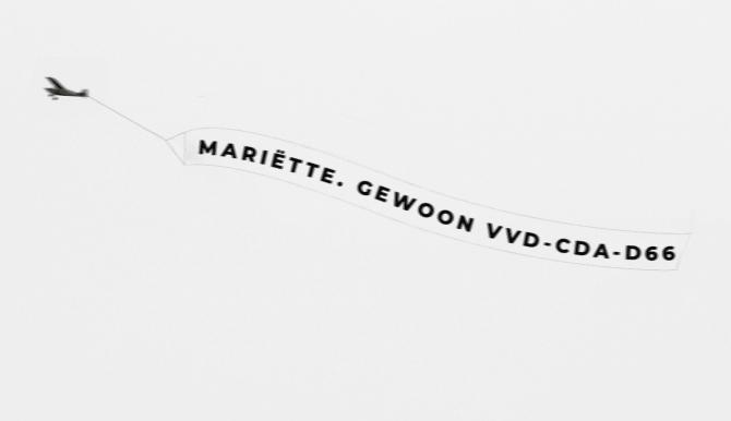 Ludieke actie: vliegtuigje vliegt over Binnenhof met tekst 'Mariëtte. Gewoon VVD-CDA-D66'
